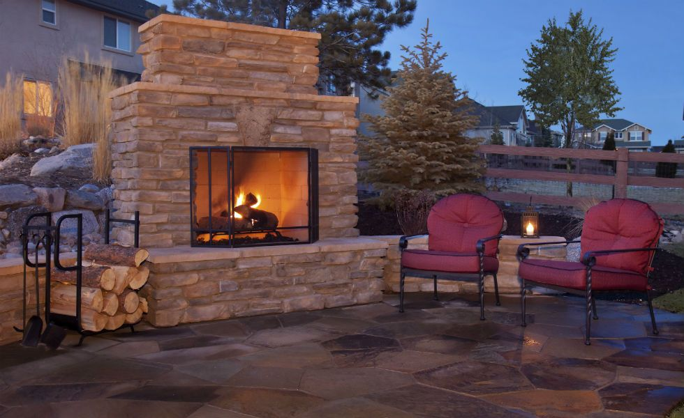 Kingwood backyard fireplace under new deck cover with fire burning