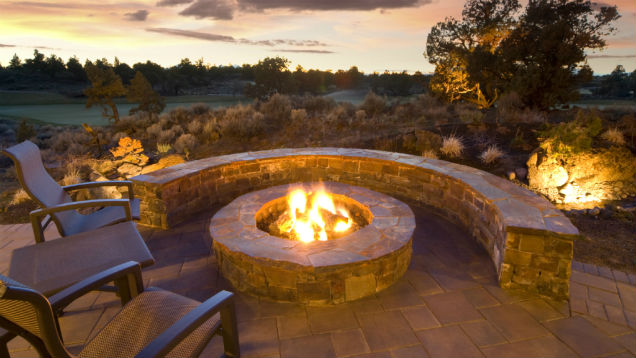gorgeous backyard fireplace with golf course backdrop